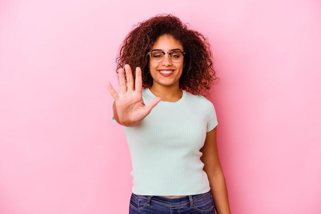 Junge afroamerikanische frau isoliert auf rosa hintergrund lächelnd fröhlich mit nummer fünf mit den fingern.