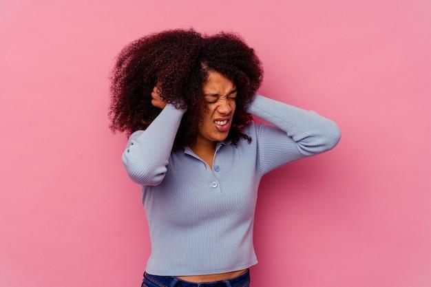 Junge afroamerikanische frau isoliert auf rosa ohren mit den händen.