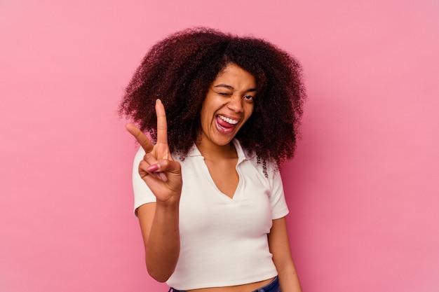 Junge afroamerikanische frau isoliert auf rosa zeigt nummer zwei mit den fingern.