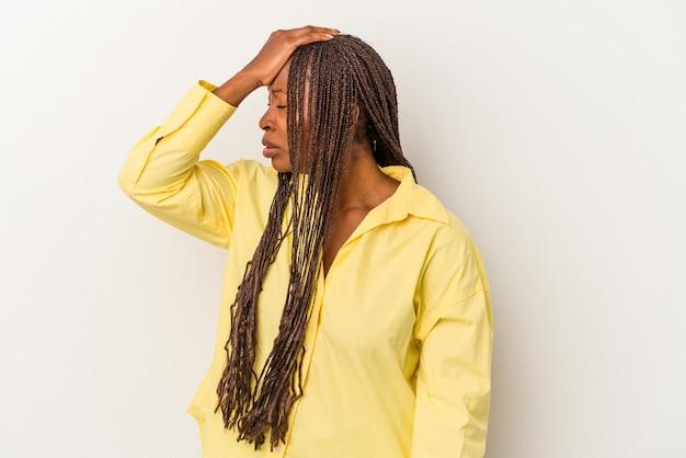 Junge afroamerikanische frau isoliert auf weißem hintergrund, die etwas vergisst, mit der hand auf die stirn schlägt und die augen schließt.