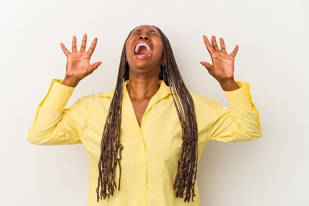 Junge afroamerikanische frau isoliert auf weißem hintergrund, die in den himmel schreit, nach oben schaut, frustriert.