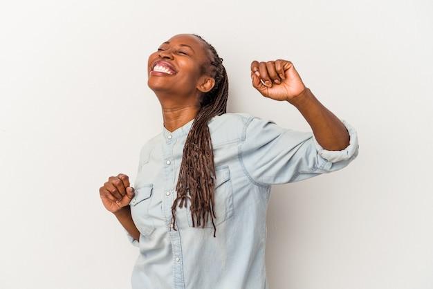 Junge afroamerikanische frau isoliert auf weißem hintergrund feiert einen besonderen tag, springt und hebt die arme mit energie.