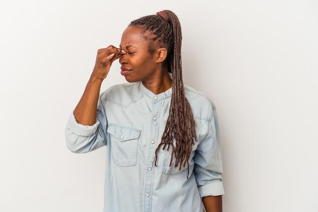 Junge afroamerikanische frau isoliert auf weißem hintergrund mit kopfschmerzen und berührt die vorderseite des gesichts.