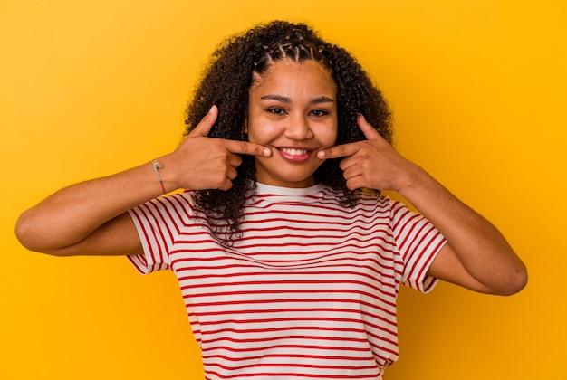 Junge afroamerikanische frau lächelt und zeigt finger auf mund.