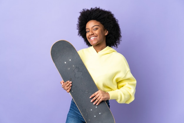 Junge afroamerikanische frau lokalisiert auf lila hintergrund mit einem skate mit glücklichem ausdruck