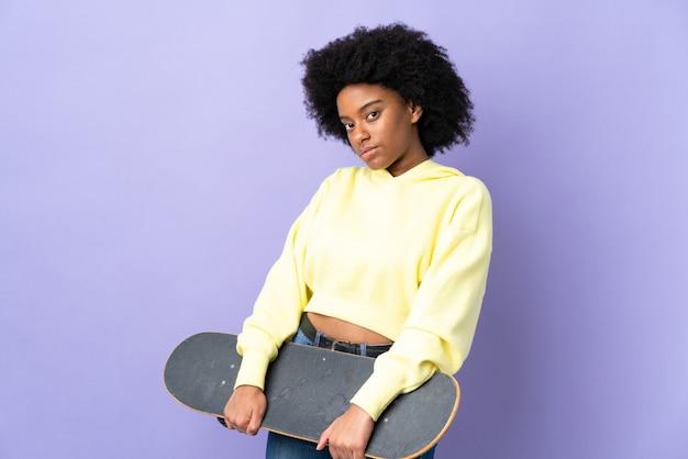 Junge afroamerikanische frau lokalisiert auf lila hintergrund mit einem skate