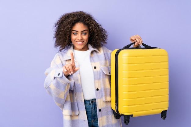 Junge afroamerikanische frau lokalisiert auf purpur im urlaub mit reisekoffer und zählen eines