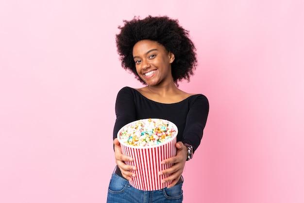 Junge afroamerikanische frau lokalisiert auf rosa hintergrund, der einen großen eimer popcorn hält