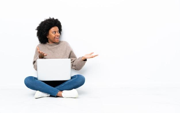 Junge afroamerikanische frau mit einem laptop, der auf dem boden mit überraschendem gesichtsausdruck sitzt
