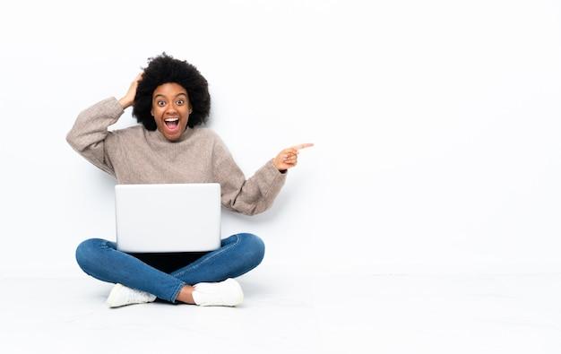 Junge afroamerikanische frau mit einem laptop, der auf dem boden sitzt, überrascht und finger zur seite zeigend