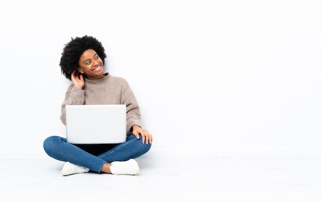 Junge afroamerikanische frau mit einem laptop, der auf dem boden sitzt und eine idee denkt