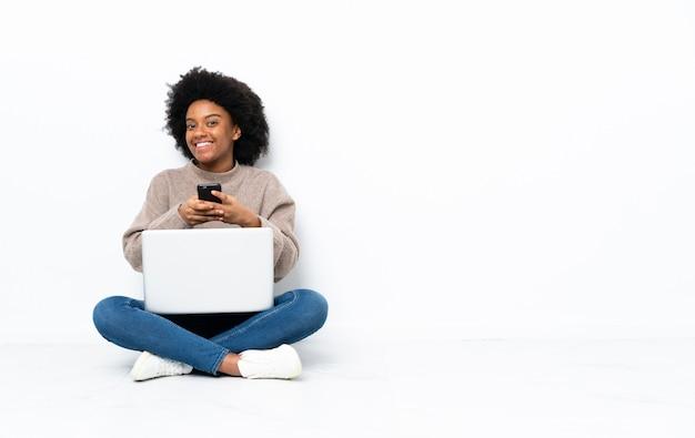 Junge afroamerikanische frau mit einem laptop, der auf dem boden sitzt und eine nachricht mit dem handy sendet
