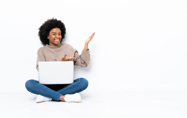Junge afroamerikanische frau mit einem laptop, der auf dem boden sitzt und hände zur seite für einladung zum kommen ausdehnt