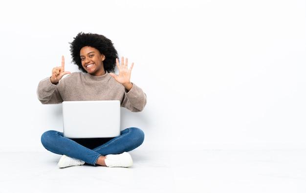 Junge afroamerikanische frau mit einem laptop, der auf dem boden sitzt und sieben mit den fingern zählt