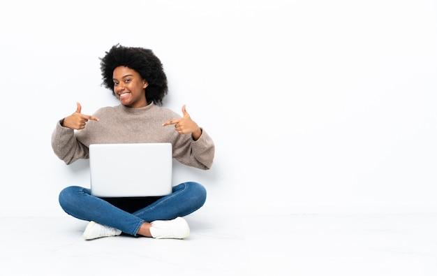 Junge afroamerikanische frau mit einem laptop, der auf dem boden stolz und selbstzufrieden sitzt