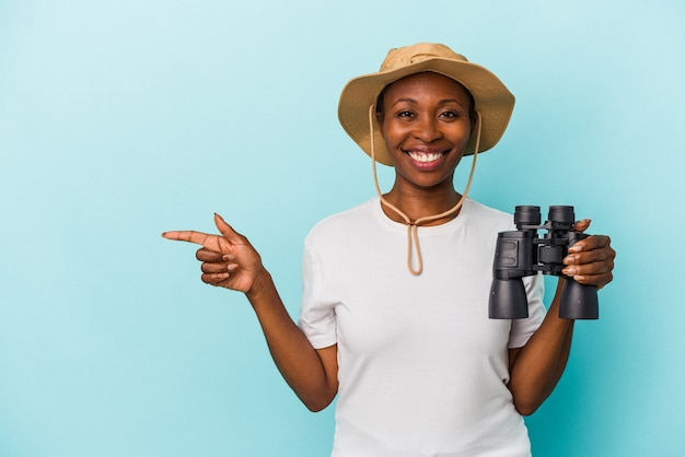 Junge afroamerikanische frau mit fernglas isoliert auf blauem hintergrund lächelnd und beiseite zeigend, etwas an der leerstelle zeigend.
