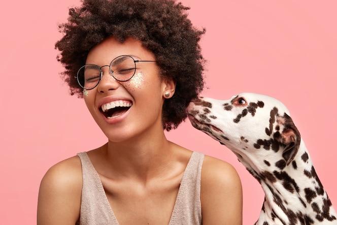 Junge afroamerikanische frau mit glitzer auf gesicht und ihrem hund