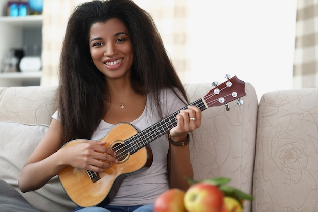 Junge afroamerikanische frau spielt musikinstrument ukuleleule