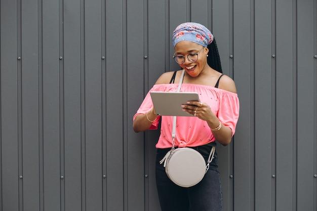 Junge afroamerikanische frau stehend und mit tablet-computer an der grauen wand