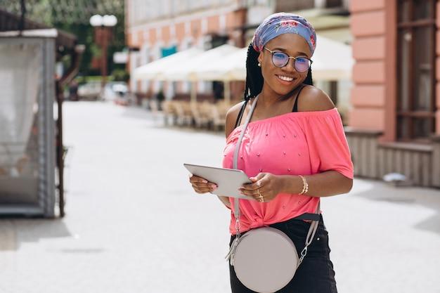 Junge afroamerikanische frau stehend und mit tablet-computer auf der straße