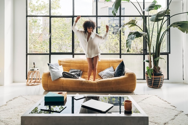 Junge afroamerikanische frau tanzt zu musik auf der couch in einem hellen wohnzimmer. home-konzept.
