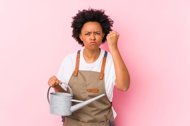 Junge afroamerikanische gärtnerfrau, die faust, aggressiven gesichtsausdruck zeigt.