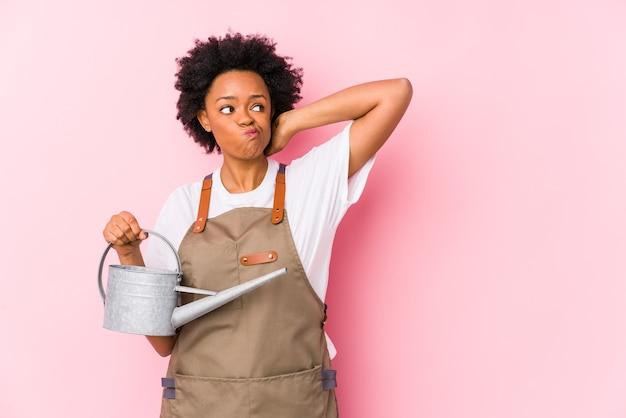 Junge afroamerikanische gärtnerin, die den hinterkopf berührt, denkt und eine wahl trifft.