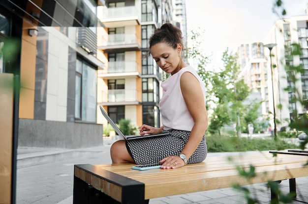 Junge afroamerikanische geschäftsfrau, die am laptop arbeitet und den bildschirm eines smartphones auf städtischem hintergrund betrachtet. unternehmerin, die laptop verwendet und plaudert. frauenfreiberuflerporträt.