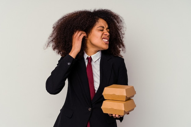 Junge afroamerikanische geschäftsfrau, die einen hamburger lokalisiert auf weißem hintergrund hält, der ohren mit händen bedeckt.