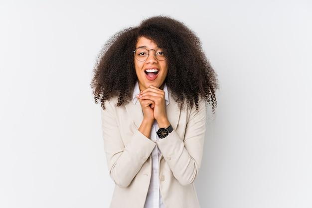 Junge afroamerikanische geschäftsfrau, die für glück betet, erstaunt und mund öffnet, der nach vorne schaut.