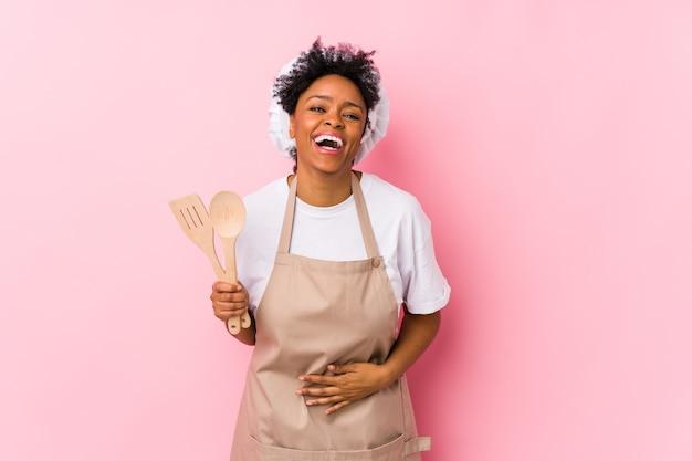 Junge afroamerikanische kochfrau, die lacht und spaß hat.