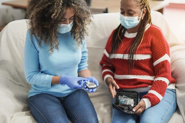 Junge afroamerikanische krankenschwester, die zu hause einen blutzucker-diabetes-test an einer afrikanischen älteren patientin wegen coronavirus-ausbruchs durchführt