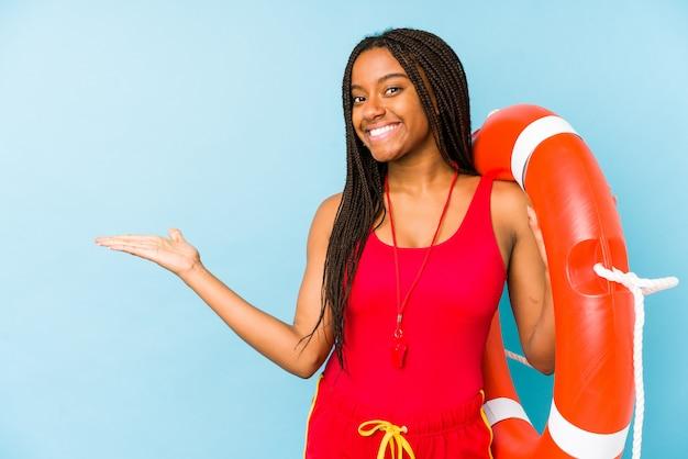 Junge afroamerikanische lebenswächterfrau isoliert, die einen kopienraum auf einer handfläche zeigt und eine andere hand auf taille hält.