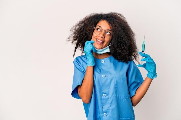 Junge afroamerikanische lockige ärztin, die eine spritze hält, entspannte das denken über etwas, das einen kopienraum betrachtet.
