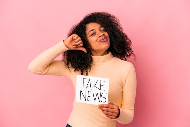 Junge afroamerikanische lockige frau, die eine gefälschte nachricht auf einem plakat hält, fühlt sich stolz und selbstbewusst, beispiel zu folgen.