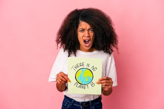 Junge afroamerikanische lockige frau, die eine planetenbotschaft auf einem plakat hält, das sehr wütend und aggressiv schreit.
