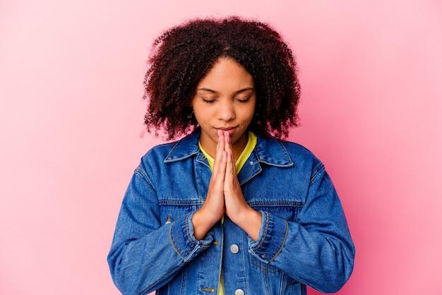 Junge afroamerikanische lockige frau isoliert, die gefühle ausdrückt