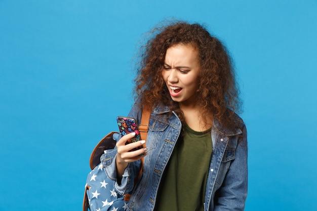Junge afroamerikanische mädchen teen studentin in denim-kleidung, rucksack halten telefon isoliert auf blauer wand phone