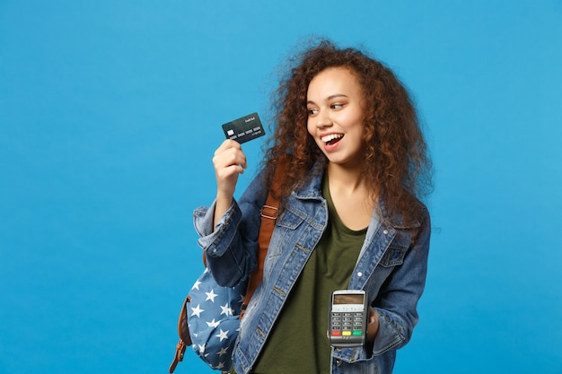 Junge afroamerikanische mädchen teen studentin in denim-kleidung, rucksack mit kreditkarte isoliert auf blauer wand