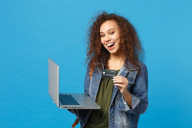 Junge afroamerikanische mädchen-teenager-studentin in denim-kleidung, rucksackarbeit am pc, bankkarte isoliert auf blauer wand halten