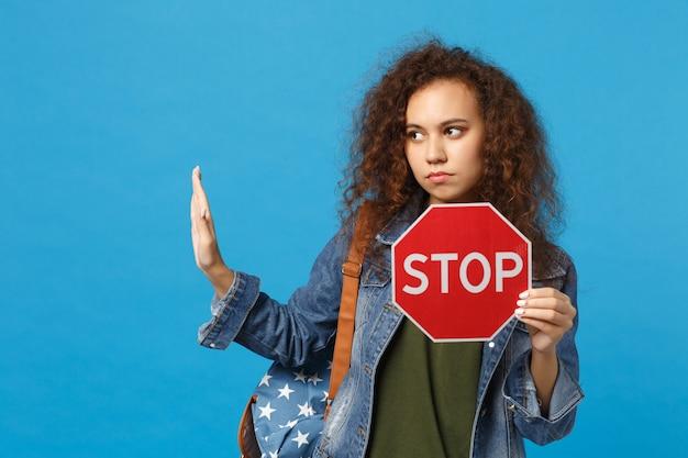 Junge afroamerikanische mädchen-teenager-studentin in denim-kleidung, rucksackhaltestopp isoliert auf blauer wand
