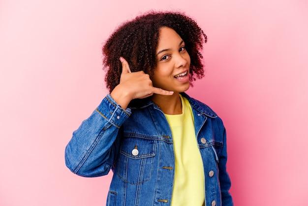 Junge afroamerikanische mischrassenfrau isoliert, die eine handy-anrufgeste mit fingern zeigt.