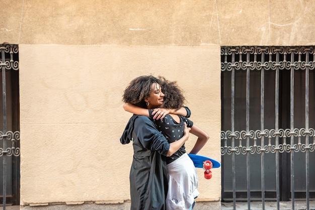 Junge afroamerikanische mutter, die ihre tochter von der schule erhält