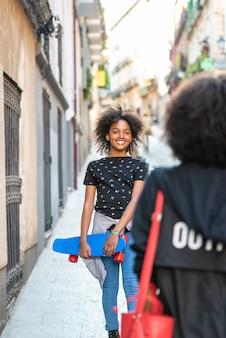 Junge afroamerikanische mutter, die ihre tochter von der schule erhält.