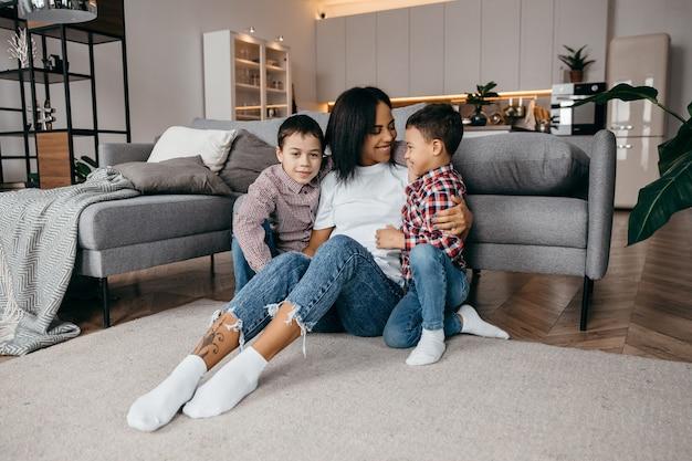 Junge afroamerikanische mutter umarmt zärtlich ihre geliebten kleinen kinder