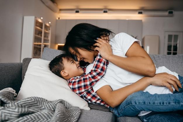 Junge afroamerikanische mutter umarmt zärtlich ihren geliebten sohn