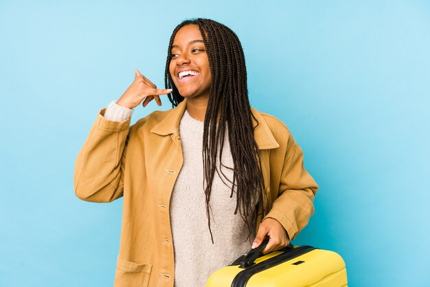 Junge afroamerikanische reisende frau, die einen koffer lokalisiert hält, der eine handy-anrufgeste mit den fingern zeigt.