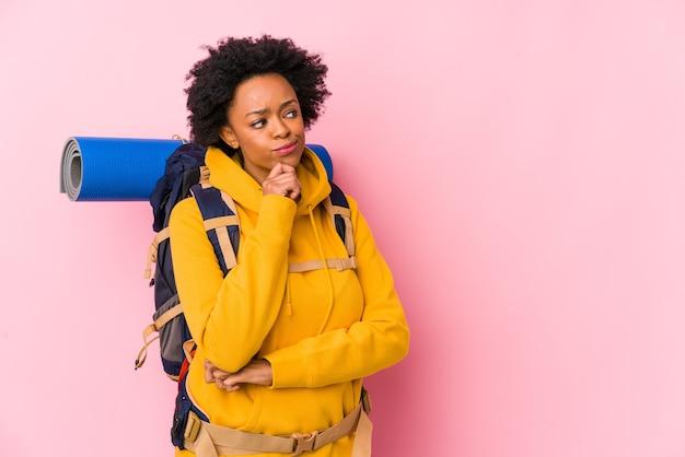 Junge afroamerikanische rucksacktouristenfrau, die seitlich mit zweifelhaftem und skeptischem ausdruck schaut.