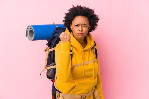Junge afroamerikanische rucksacktouristenfrau isoliert, die faust, aggressiven gesichtsausdruck zeigend zeigt.