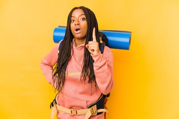 Junge afroamerikanische rucksacktouristenfrau isoliert mit einer idee, inspirationskonzept.